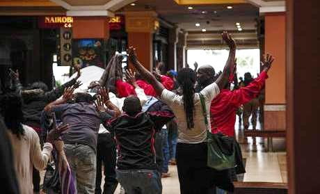 epa03877744 People walk with their hands in the air at the Westgate shopping mall after a shootout in Nairobi, Kenya, 21 September 2013. Gunmen fired automatic weapons and grenades inside an upmarket shopping mall in Kenyas capital Nairobi on 21 September, killing at least 30 people and injuring more than 50, the Kenyan Red Cross said. Somali Islamist group Al-Shabaab claimed responsibility for the siege, and police have arrested one of the gunmen, an official confirmed.  EPA/KABIR DHANJI