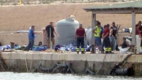I corpi di alcuni migranti sul molo del porto di Lampedusa, 3 ottobre 2013. E' di 94 vittime, tra cui donne e bambini, e 151 superstiti il bilancio provvisorio del naufragio avvenuto stamani davanti alle coste di Lampedusa. Secondo i racconti dei sopravvissuti sul barcone viaggiavano infatti circa 500 migranti. All'appello mancherebbe dunque circa 250 dispersi, anche se non ci sono conferme ufficiali su questo numero. ANSA/FARKAS