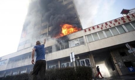 A man points as people attempt to put out a blaze at a government building in Tuzla