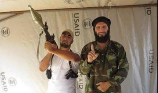 ISIS Commander Muhajireen Kavkaz wa Sham standing in a tent marked USAID